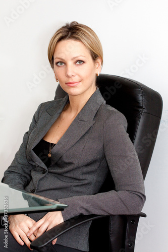 Business woman in black chair with short haircut