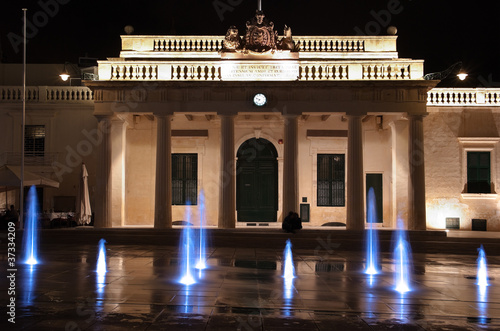 coloured jets water of fountain and the Main Guard building by night in Valletta, Malta