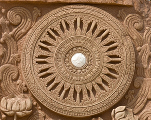 carving on stone the wheel of law symbol of buddhism