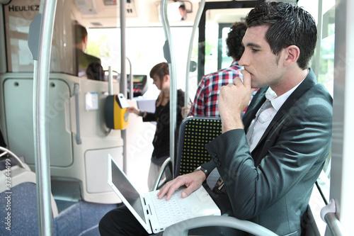 Leinwandbild Motiv Commuter on a bus with a laptop