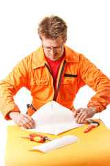 worker carefully folds a paper sheet