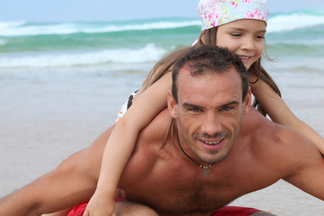 a little girl and her father playing on the beach