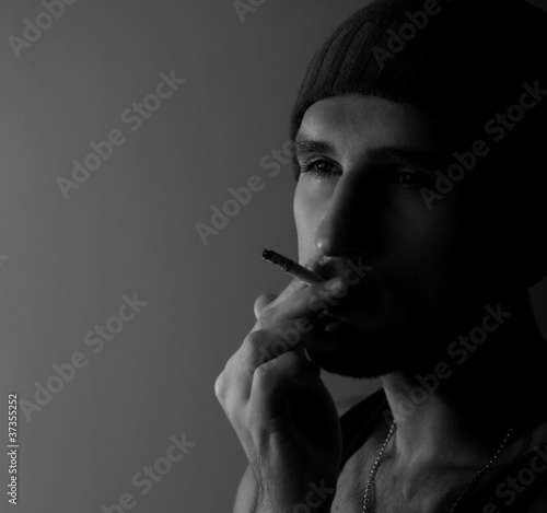 lonely young man with a cigarette in the dark