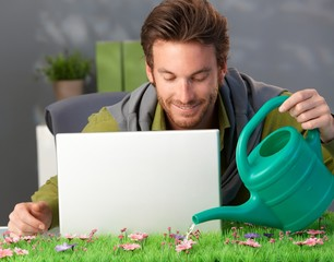 Man watering spring table with laptop
