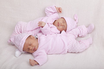 identical twin girls sleeping on a sofa