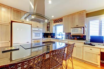 Luxury new kitchen with light cbainets and dark island.