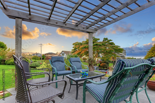 Sunset over garden gazebo with chairs.