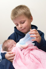 Six year old sibling feeding newborn baby sister.