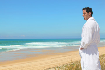 Man on the beach in towelling robe
