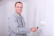 Man in overalls painting a room white