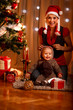Mother and adorable baby in suit of Santa's little helper
