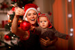 Mother showing Christmas ball  to baby near Christmas tree - 37375054