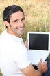 Smiling man using a laptop with a blank screen in a field