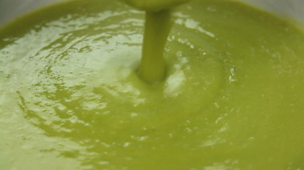 Pea soup being poured into a bowl with a ladle.