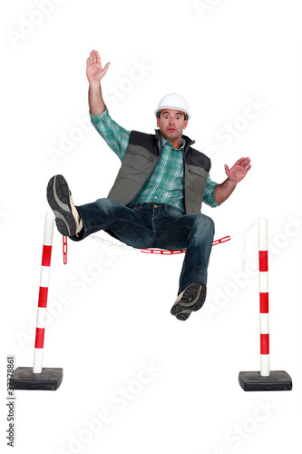 Workman falling over a safety barrier