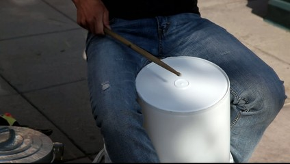 video of a person playing drums on the streets with bucket