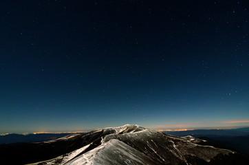 Glittering stars above snowy autumn mountain ridge