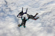 Three skydivers in freefall over a bank of clouds - 37382809