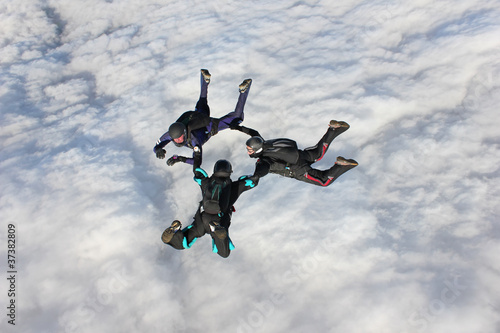 Three skydivers in freefall over a bank of clouds