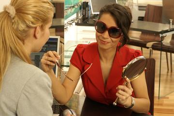 Frau sucht sich beim Optiker eine Sonnenbrille aus