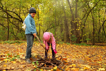 brother and sister in autumn park poke sticks in old rusty hatch