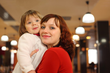 mother with little smiling daughter stand in empty cafe