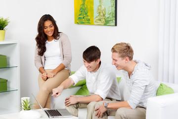 lachende junge menschen schauen aufs laptop