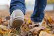 Walking in sport shoes on leaves in autmn day