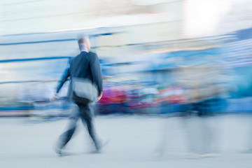 Motion blured businessman rushing to office in a city