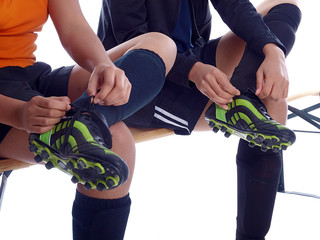 girls tying up their soccer shoes