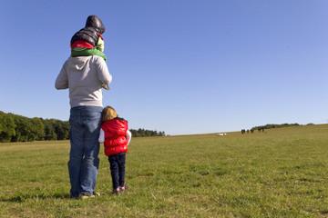 Vater und seine Kinder beobachten eine Schafherde