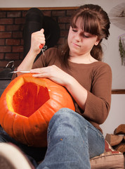 young girl carving a pumpking