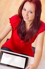 Frau sitzt mit Tablet PC am Schreibtisch