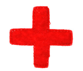 Medical red cross symbol made of fabric on white background