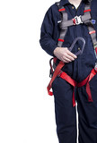 man wearing coveralls and fall protection harness and lanyard