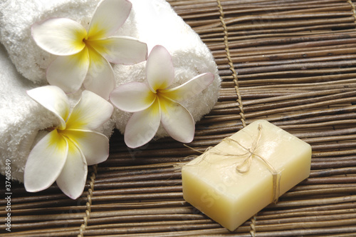 Frangipani flower with towel and natural handmade soap on mat