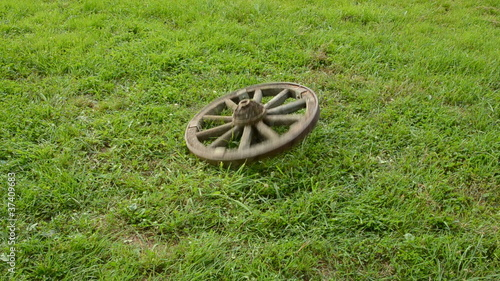 two old wheels rolling on the garden grass