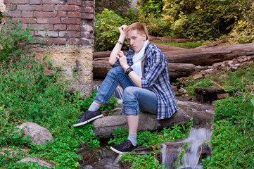Young human is siting among greenery