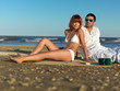 young couple relaxing by the sea shore
