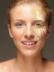 woman with colored powders on face laughing