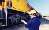 worker checking train engine