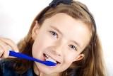 Girl brushing teeth on white background