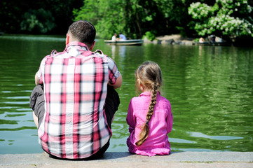 Young father and his daughter near the pond