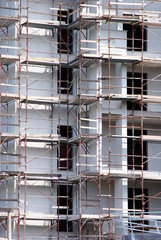 building under construction with rusted scaffold