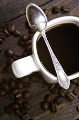 Czarna kawa na drewnianym stole z łyżeczką