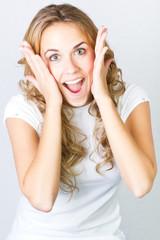 studio portrait of a beautiful blonde girl surprised