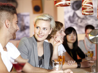 Young couple sitting at the bar with friends