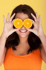 Joyful Woman With Orange Slices Over Eyes