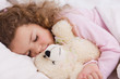 Girl hugging her teddy while sleeping