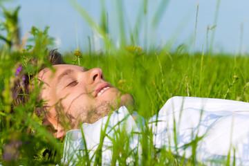 Mann liegt auf einer Wiese und träumt